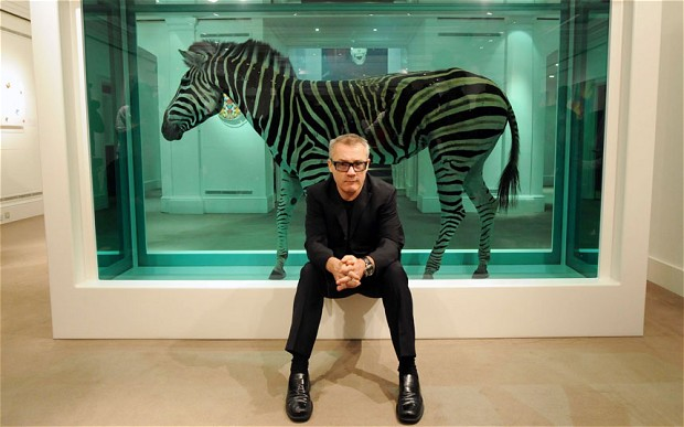 "Damien Hirst poses in front of ""The Incredible Journey"" featuring a Zebra in formaldehyde."