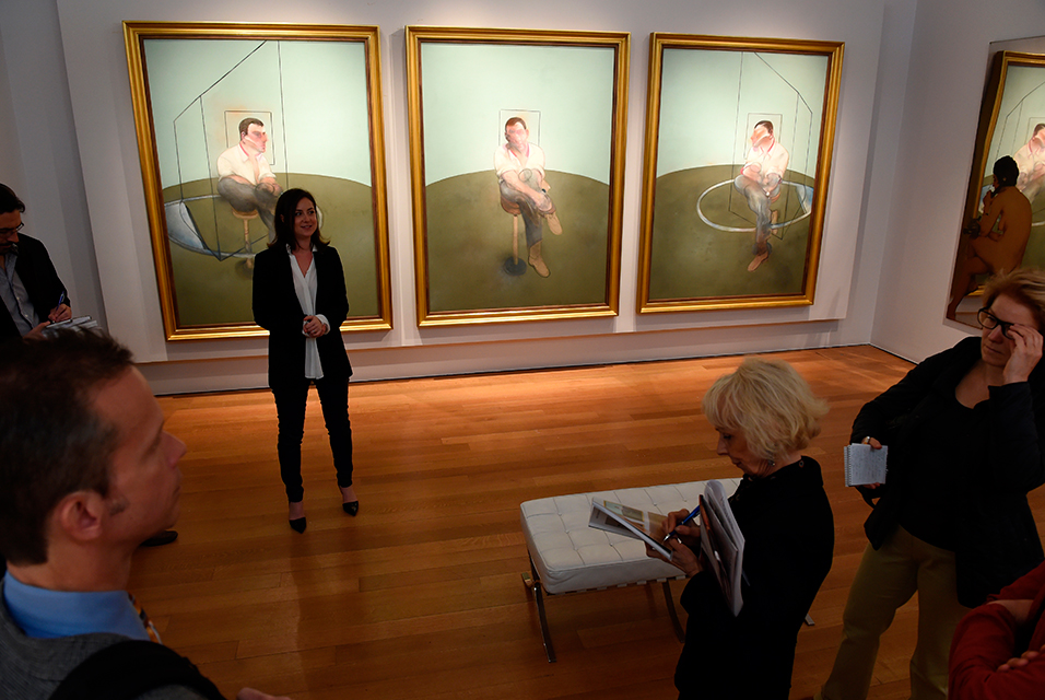 """Sara Friedlander, Post-War and Contemporary Art expert, speaks in front of Francis Bacon's """"Three Studies for a Portrait of John Edwards"""", painted in 1984, on display May 2, 2014 during a preview of the Impressionist and Modern Art sale at Christie's that will take place May 6 in New York. The painting is estimated at USD $75 million. AFP PHOTO/Stan HONDA."""